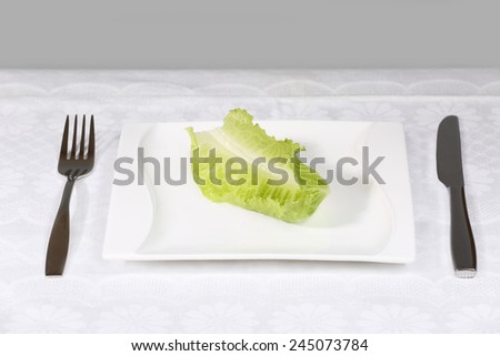 Diet, weight loss, low calories food concept - single green salad leaf on plate with fork and knife on the table - stock photo