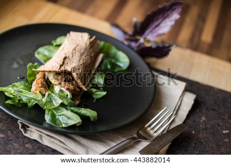 Diet wrap with meat and greens in a black plate
