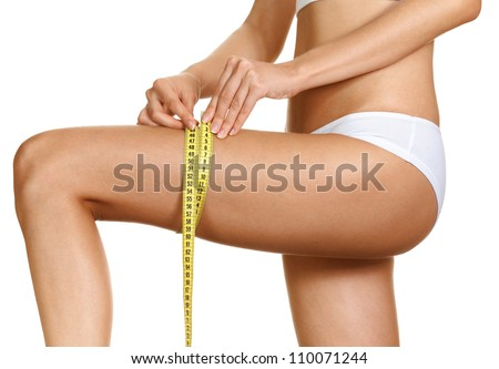 Diet - young woman is measuring her thigh with measuring tape - stock photo