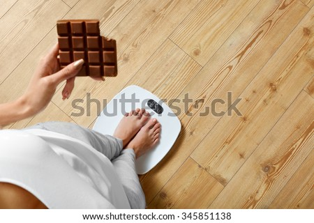 Diet. Young Woman Standing On Weighing Scale And Holding Chocolate Bar. Sweets Are Unhealthy Junk Food. Sugar Is Bad For Health. Dieting, Healthy Eating, Lifestyle. Weight Loss. Top View - stock photo