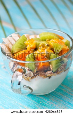 Dietary breakfast. Muesli, yoghurt, tropical fruits: mango, kiwi, pineapple, passion fruit in cup on a blue background - stock photo