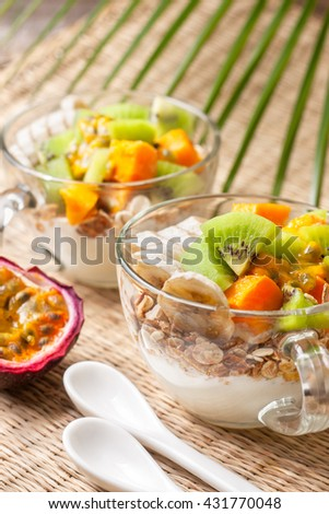 Dietary breakfast. Muesli, yoghurt, tropical fruits: mango, kiwi, pineapple, passion fruit in cup on a straw background - stock photo