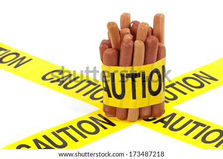 Dietary fast food warning, caution of high cholesterol and saturated fat, unhealthy nutrition concept image (Variety of beef sausages, wieners and hot dogs wrapped in yellow caution tape) - stock photo