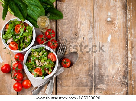 Dietary food background: vegetable salad with spinach, cherry tomatoes, barley porridge and olive oil on an old wooden board, vegan cuisine - stock photo