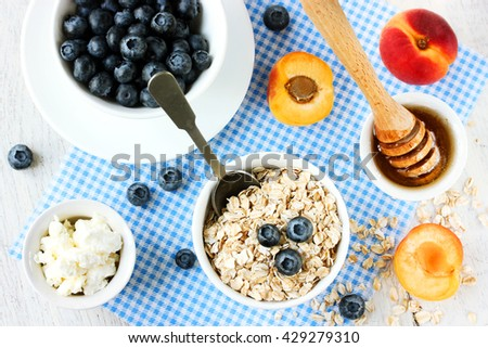 Dietary food for weight loss - oatmeal, berries, fruits, honey, cottage cheese top view - stock photo