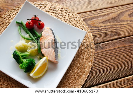 Dietary food. Salmon steak and steamed vegetables, served on a wooden background. Lenten  healthy dietary food. Top view on dietary fish dish with salmon and vegetables - stock photo