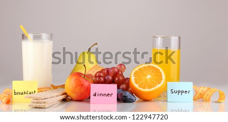 Dietary foods for breakfast, dinner and supper on grey background