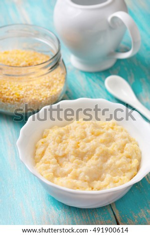 Dietary healthy breakfast. White cup with corn porridge on a blue wood background