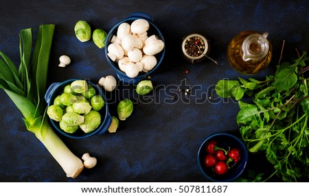 Dietary menu. Ingredients: Brussels sprouts, mushrooms, leeks and herbs on a dark background. Top view.