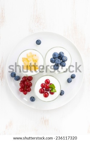 dietary product - assortment yogurt with fresh berries in glass jar, top view, vertical - stock photo