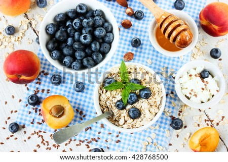 Dietary products - oatmeal, fresh berries and fruit, flax, honey, cottage cheese for breakfast on a white table top view - stock photo