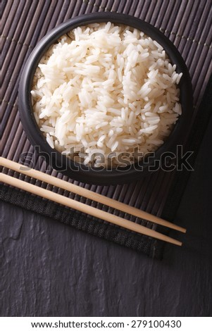 Dietary rice in a black bowl close-up and chopsticks. vertical top view  - stock photo