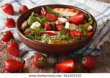 Dietary salad with strawberries, grilled chicken, brie and arugula close-up on the table. Horizontal - stock photo