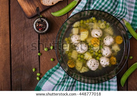 Dietary soup with chicken meatballs and green peas in a glass bowl on a wooden background. Top view - stock photo