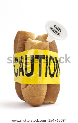 Dietary warning or gluten/wheat allergy warning (Fresh bread rolls wrapped in yellow caution tape, with Tasty Gluten tag - easy to remove text, on white background) - stock photo
