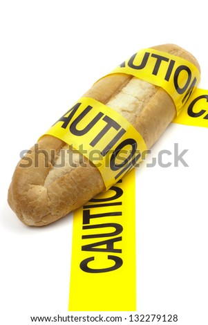 Dietary warning or gluten/wheat allergy warning (Loaf of bread wrapped in yellow caution tape) - stock photo
