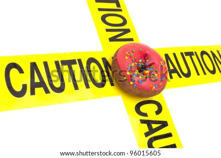 Dietary warning, or high calorie/high, fat junk food warning (Doughnut placed on top of yellow caution tape) - stock photo