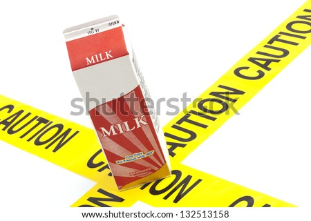 Dietary warning or lactose intolerance allergy warning (generic carton of milk on top of yellow caution tape) - stock photo