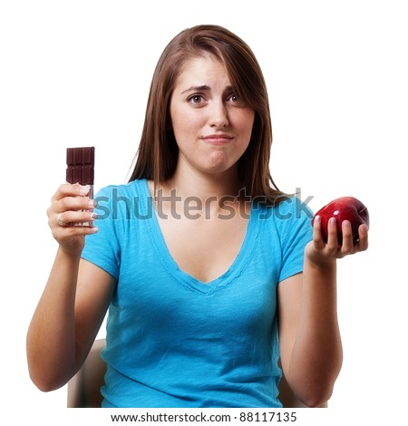 Dieter's decision:  young girl trying to decide between a healthy apple or a delicious chocolate bar for a snack - stock photo
