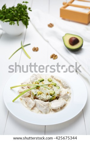 Dietetic turkey or chicken fillet with cream sauce, rice, avocado and nuts. Healthy diet food. Restaurant menu meal in white plate. - stock photo