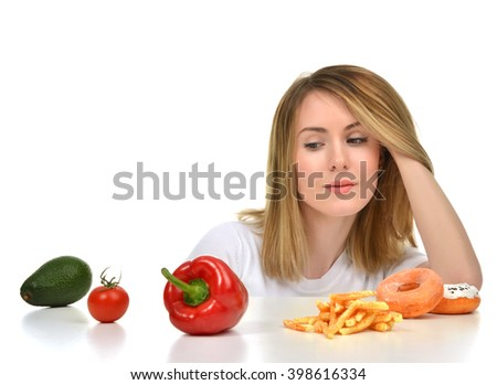 Dietician woman looking at vegetables avocado tomato pepper and fast food french fries and sweet unhealthy donuts isolated on white background. Diet nutrition healthy lifestyle concept.