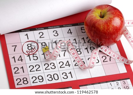 Dieting concept apple and tape measure on a calendar with a date to start a diet - stock photo
