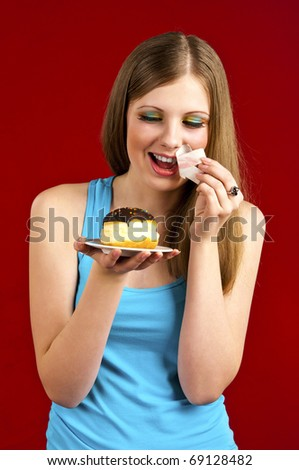 Dieting concept: attractive girl with doughnut removing sticky tape from her mouth.
