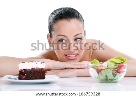 Dieting concept,  beautiful young woman choosing between healthy food and tasty cakes - stock photo