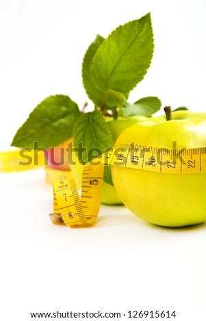 dieting. green, yellow apple with leaf and tape isolated on a white background - stock photo