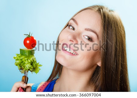 Dieting, healthcare and weight loss concept. Sporty girl fitness woman with measuring tape on neck and holding fork with fresh mixed vegetables on blue background. Studio shot. - stock photo
