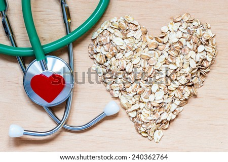 Dieting healthcare concept. Oat cereal heart shaped, stethoscope on wooden surface. Healthy food for lowering cholesterol, protect heart. - stock photo