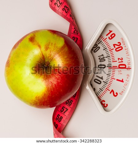 Dieting healthy eating slim down concept. Closeup apple with measuring tape on weight scale