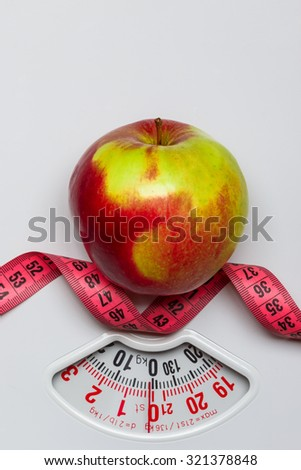 Dieting healthy eating slim down concept. Closeup apple with measuring tape on white weight scale - stock photo