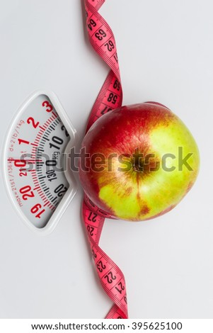 Dieting healthy eating slim down concept. Closeup apple with measuring tape on white weight scale