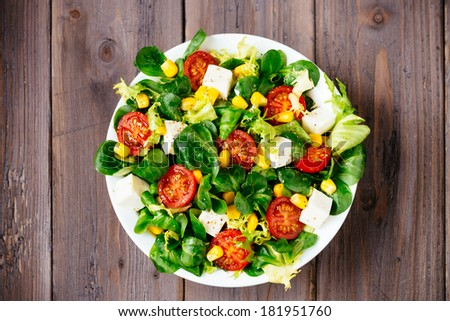 Dieting healthy salad  on rustic wooden table top view. Mixed greens, tomatos, diet cheese, olive oil and spices for healthy lifestyle concept. - stock photo