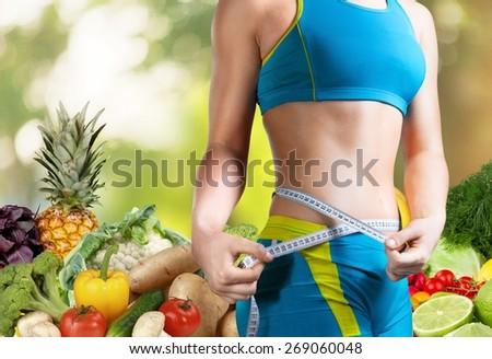 Dieting. Measuring tape around slim beautiful waist. - stock photo
