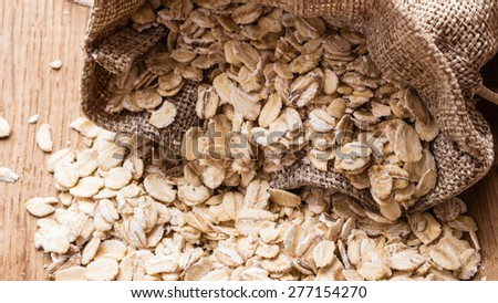 Dieting. Oat cereal in burlap sack on wooden surface. Healthy food for lowering cholesterol, protect heart. - stock photo