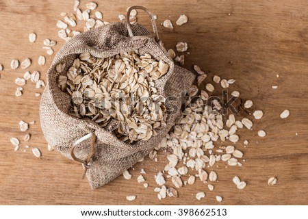 Dieting. Oat cereal in burlap sack on wooden surface, top, view. Healthy food for lowering cholesterol, protect heart.