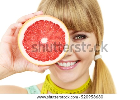 Dieting weight loss health care concept. Woman with yellow measuring tape on neck holds grapefruit isolated on white