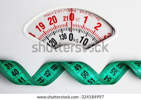 Dieting weightloss slim down concept. Closeup measuring tape on white weight scale