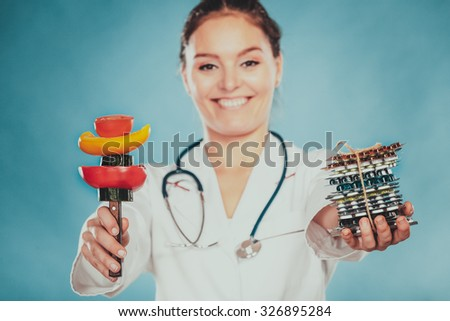 Dietitian nutritionist woman holding diet weight loss tablets pills and vegetables. Choice between natural and synthetic way of slimming dieting. Health care. Instagram filter. - stock photo