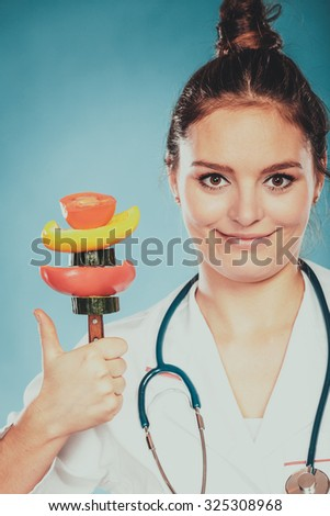 Dietitian nutritionist woman with thumb up holding fork with fresh vegetables like tomato, pepper and cucumber. Dieting and slimming. Healthy nutrition. - stock photo