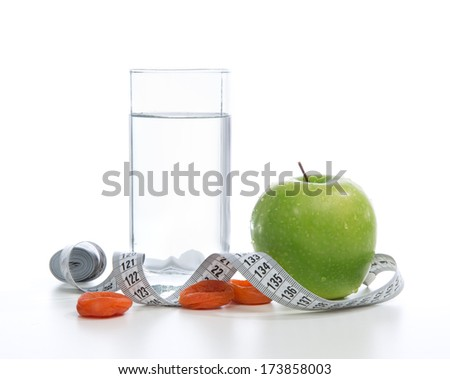 Dietting breakfast diabetes weight loss concept with tape measure organic green apple glass of drinking water and dried apricots on a white background