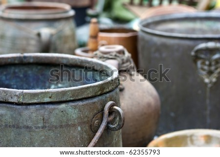 Different ancient iron and clay kettles and pots - stock photo