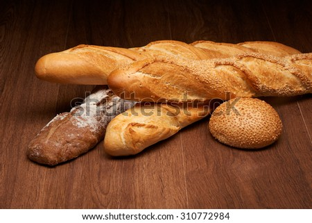 Different baguette breads and bun on dark wooden table background - stock photo