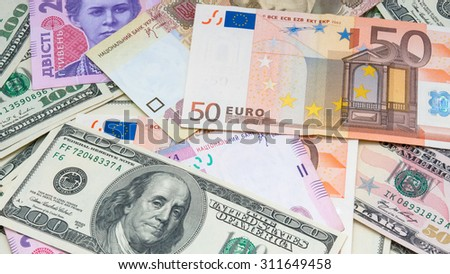 Different banknotes (dollar, euro, hryvnia) make money background - stock photo