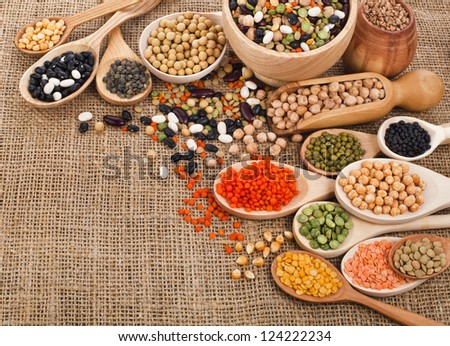 different beans, legumes, peas, lentils in spoon on the sackcloth background