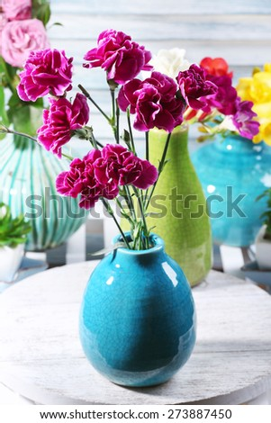 Different beautiful flowers in vases on table close up - stock photo