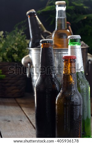 Different beers on a table of wood. There are bottle and glass with ice to keep them cold - stock photo