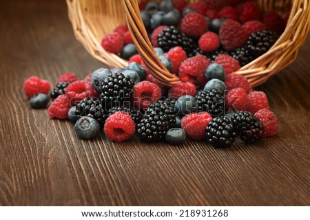 different berries (blueberries raspberries blackberries) in a basket on a wooden table - stock photo